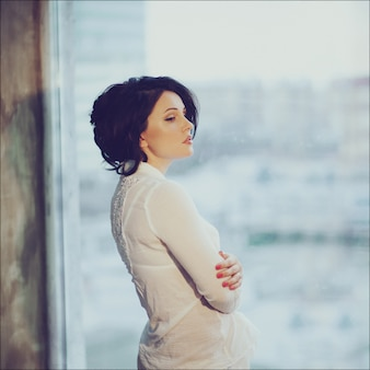 Romantic portrait of a beautiful young brunette in white shirt staying by the window