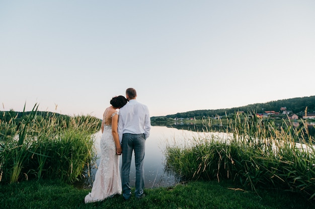 Romantic portrait from behind of wedding couple standing together on shore at sunset and enjoying lake view.