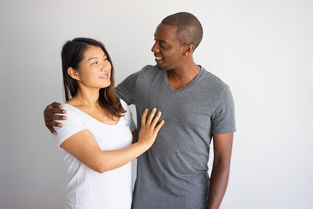 Romantic portrait of interracial couple smiling to each other.