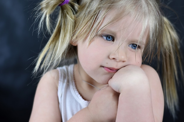 Romantic portrait of a little girl on a black background