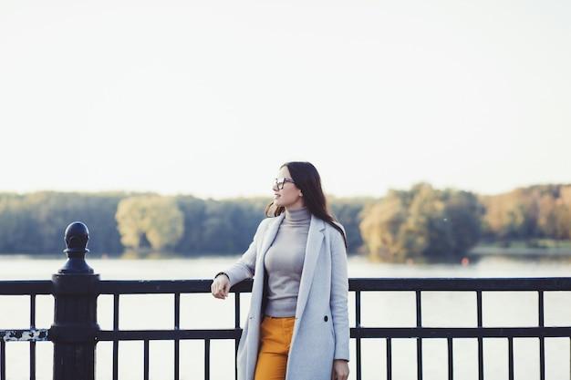 空に対して秋の公園で美しい女性のロマンチックな肖像画