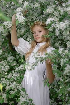 개화 사과 나무 근처 공원에서 여자의 낭만적인 초상화. 천연 화장품. 흰 드레스를 입은 여성의 자연미