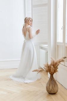 집에서 아름 다운 긴 흰색 드레스에 창 근처 여자의 낭만적인 초상화. 소녀는 파란 눈과 아름다운 화장을 한 얼굴에 금발입니다. 천연화장품