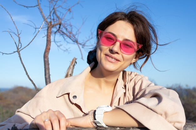 木、森に対してジーンズレトロなメガネで巻き毛を持つ若い女性のロマンチックな肖像画。自然の中で創造的な肖像画の女性。デザインアートのコンセプト