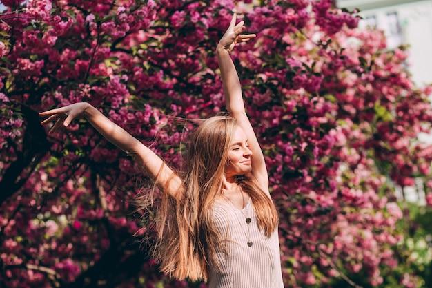 Романтический портрет очаровательной блондинки на стене цветущего сада. дерево с розовыми цветами. красота блондинка с длинными волосами на открытом воздухе. цветение вишни. крупным планом портрет. сакура