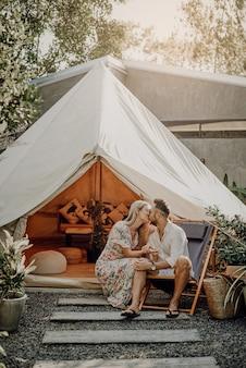 Романтический портрет пары, празднующей медовый месяц в отпуске и туре в таиланде. любящая жена и муж целуются на фоне палатки и природы в солнечный день.