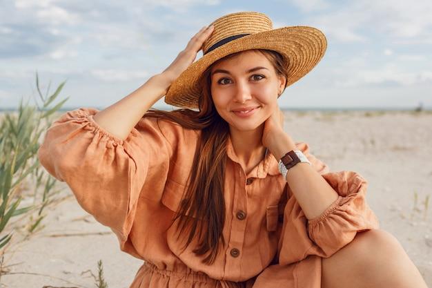 麦わら帽子とスタイリッシュなリネンのドレスで笑顔の女性のロマンチックな肖像画。海の近くに身も凍るような夢のような女の子。夏のファッショントレンド。
