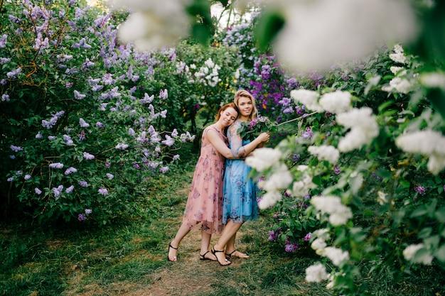 Романтический портрет сестер-близнецов в нежных платьях, позирует в парке летом.