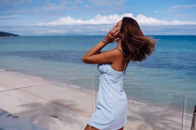 熱帯のビーチ、晴れた日、日焼けした黒い肌に一人で青い光のドレスを着た女性のロマンチックな肖像画