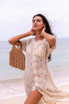 風の強い曇りの日にビーチで長いドレスを着た女性のロマンチックな肖像画。