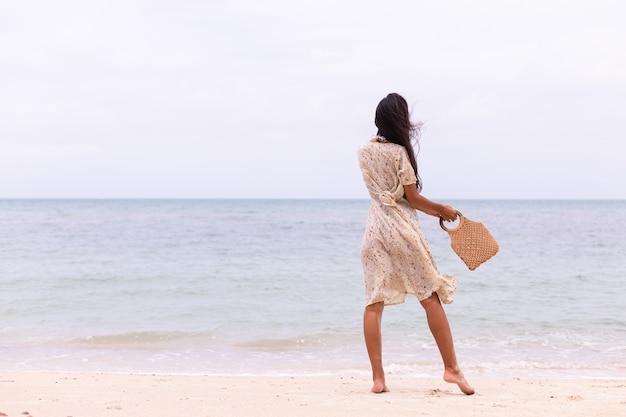 Романтический портрет женщины в длинном платье на пляже в ветреный пасмурный день.
