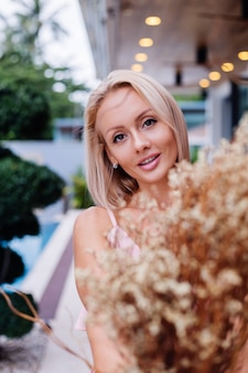 ピンクの夜のかわいいドレスを着た女性のロマンチックな肖像画は、豪華な熱帯の別荘の外で野生の花を保持します花束と美しい女性
