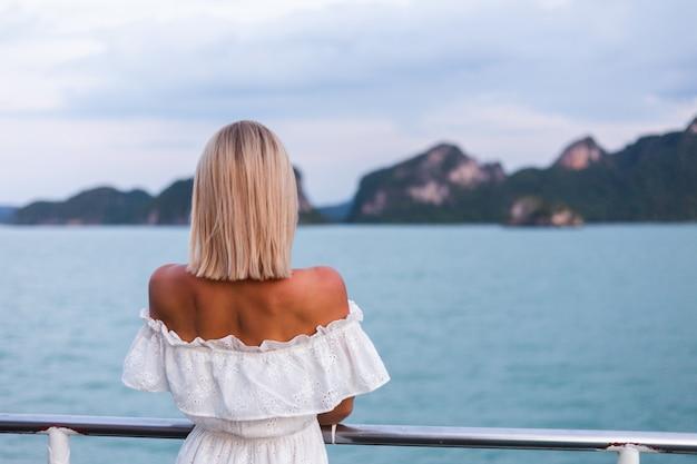 Романтический портрет женщины в белом платье, плывущей на большой лодке-пароме