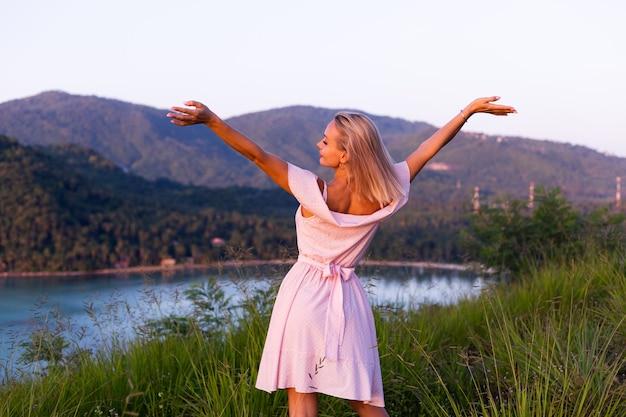 素晴らしい熱帯の海の景色を望む山の公園でリラックスを楽しんでいる夏のドレスを着た若い白人女性のロマンチックな肖像画タイ周辺の休暇旅行の女性日没の幸せな女性