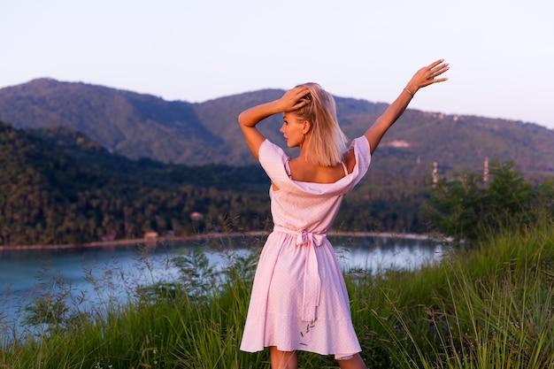 Романтический портрет молодой кавказской женщины в летнем платье, наслаждаясь отдыхом в парке на горе с удивительным тропическим видом на море. женщина в отпуске путешествует по таиланду. счастливая женщина на закате.