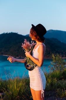 素晴らしい熱帯の海の景色を望む山の公園でリラックスを楽しんで夏のドレスを着た若い白人女性のロマンチックな肖像画