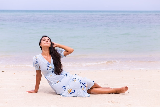 Ritratto romantico di donna in abito lungo blu sulla spiaggia in riva al mare in una giornata ventosa