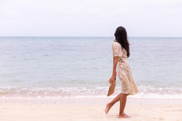 Romantico ritratto di donna in abito lungo sulla spiaggia al ventoso giorno nuvoloso.