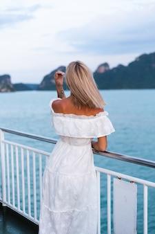 Ritratto romantico della donna in vestito bianco che naviga sul grande traghetto della barca