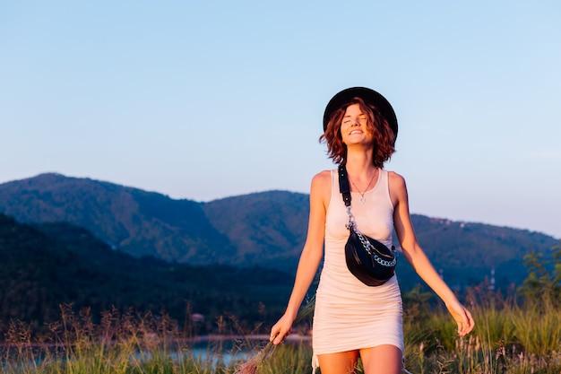 Ritratto romantico di giovane donna caucasica in abito estivo godendo di relax nel parco sulla montagna con incredibile vista sul mare tropicale femmina in vacanza viaggia in thailandia donna felice al tramonto