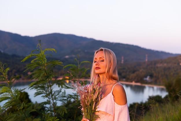 Ritratto romantico di giovane donna caucasica in vestito da estate che gode del relax nel parco sulla montagna con splendida vista sul mare tropicale