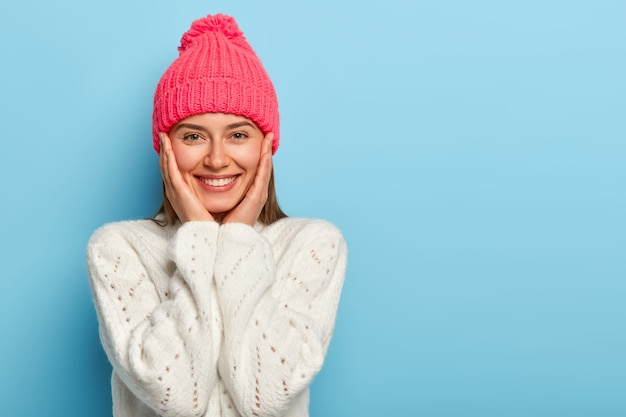 Romantic positive young european woman smiles gently, has white perfect teeth, touches both cheeks, has friendly look, wears pink hat with pompon and white sweater