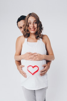 Romantic pregnancy. man hugging pregnant wife. heart on the belly. valentine day