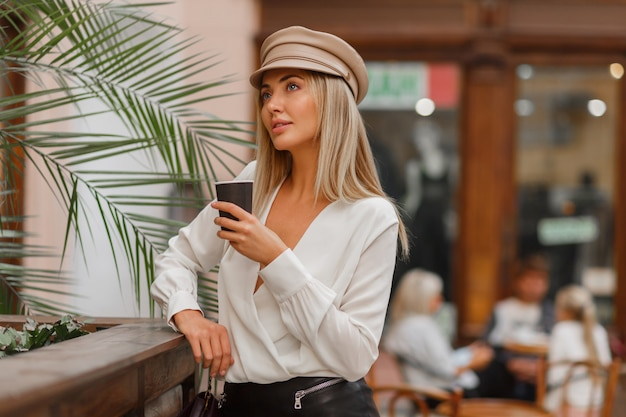 Romantic  pretty  blond woman enjoying hot coffee outdoor