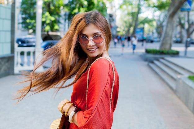 夏の日当たりの良いヨーロッパの都市でポーズをしながら肩越しに見ているロマンチックなかなり若い女性。明るいサンゴのドレス。