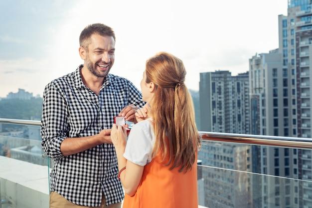 ロマンチックなプロポーズ。建物の上に立っている間彼と結婚するために彼のガールフレンドを提供する楽しい幸せな男