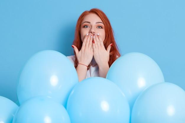 誰かにキスを吹く準備ができているロマンチックな赤い髪の女性、パーティー気分、気球で青い壁にポーズをとる、女性は彼女の誕生日パーティーを楽しんで、彼女の唇に手のひらで立っています。