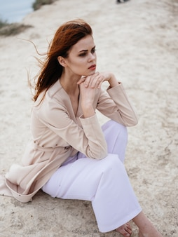 ロマンチックな赤毛の女性屋外の自然に軽いセーターを着ています。高品質の写真