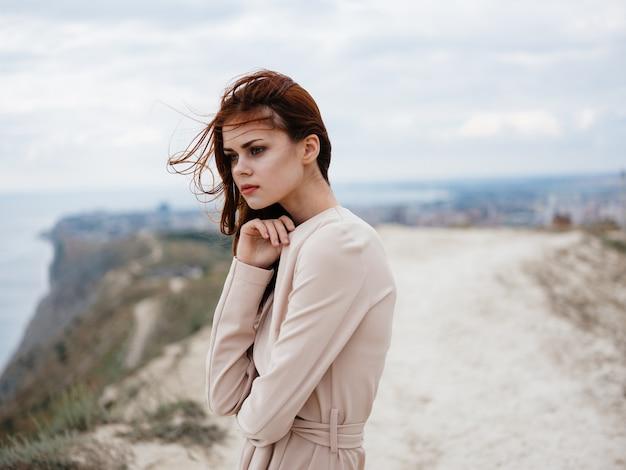 ロマンチックな赤毛の女性屋外の自然の軽いセーターで