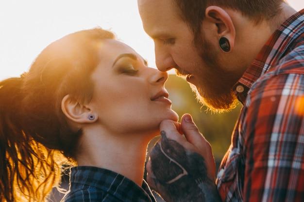 낭만적인 관계입니다. 부드러운 사랑의 조화. 석양에 키스 하는 행복 한 빨간 머리 hipster 커플입니다.