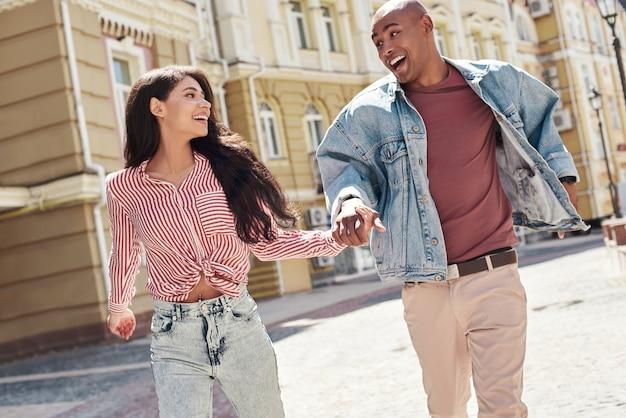 Романтические отношения молодая разнообразная пара, бегущая по улице города, держась за руки, глядя на каждого