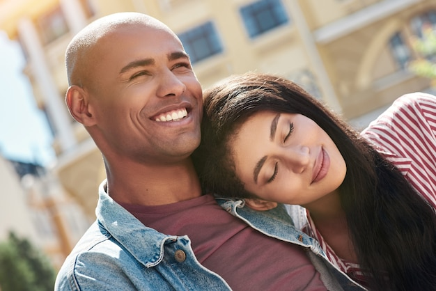 Romantic relationship young diverse couple sitting on the city street hugging girlfriend sleeping on