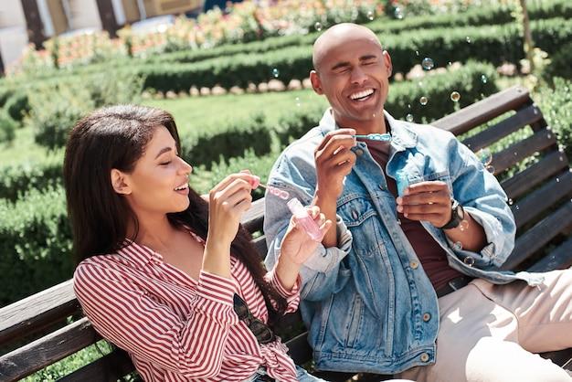 Романтические отношения молодая разнообразная пара, сидящая на скамейке на городской улице, пускает мыльные пузыри