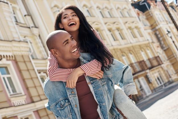 Романтические отношения молодая разнообразная пара гуляет по улице города парень несет подругу