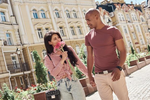 Романтические отношения молодая разнообразная пара гуляет по улице города, держась за руки, говорящая девушка