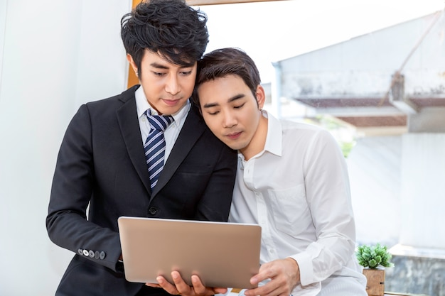 Romantic and relax time. asian homosexual couple in suite shopping online with laptop computer together at home. concept lgbt gay.