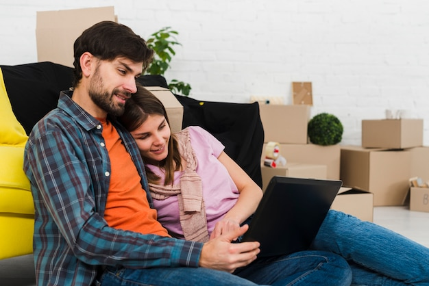 Romantic relaxed young couple at modern home using laptop