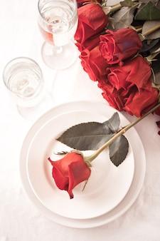 장미, 접시, 안경이 있는 2인용 로맨틱 레스토랑 테이블.