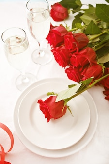Romantic restaurant table setting for two with roses, plates and glasses.