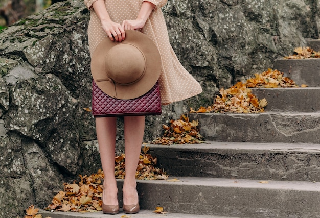 Romantic retro image of a girl below the waist in a light beige dress with white polka dots developing in the wind. in the girl's hands is a beige hat and a burgundy handbag.