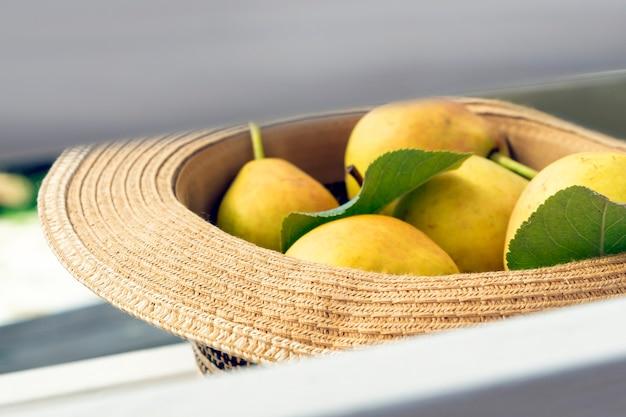 모자와 익은 유기농 배가 있는 낭만적인 소박한 정물. 가을 - 여름 원예 구성. 수확. 초라한 시크 스타일