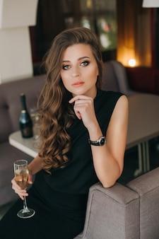 긴 머리를 가진 로맨틱 슬픈 여자는 샴페인 잔을 보유하고 있습니다. 화려한 긴 건강한 머리카락.