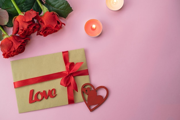 Romantic saint valentine pink background card with bouquet of beatiful red roses and love gift envelope