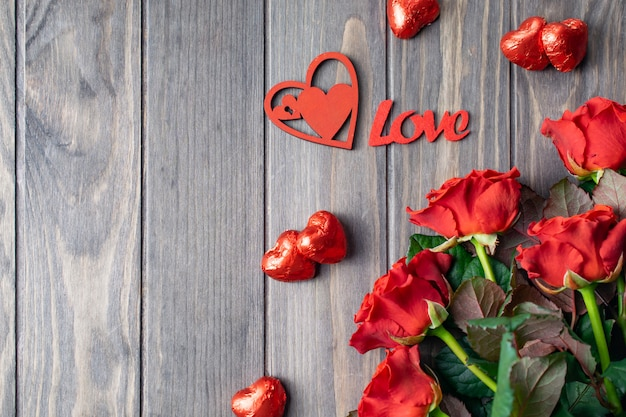 Romantic saint valentine wooden background card with bouquet of beatiful red roses and love lettering
