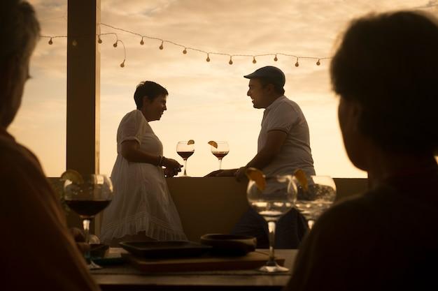 테라스에서 화려한 골드 일몰 동안 관계에서 함께 칵테일을 마시는 cacuasian 중년 사람들의 부부와 함께 낭만적 인 장면