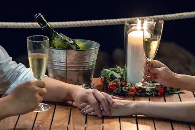 結婚式のお祝いの新郎新婦のロマンチックな画面は夜にシャンパンと一緒に手を握っていた
